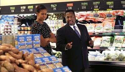 First lady Michelle Obama walks through Sterling Farms Grocery Store with actor Wendell Pierce