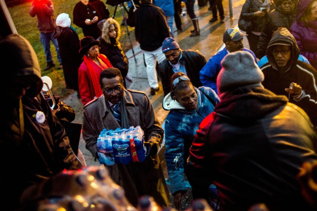 Flint residents line up for free bottled water as activists protest outside of City Hall to protest Michigan Gov. Rick Snyder's handling of the water crisis Friday, Jan. 8, 2016 in Flint. Mich. (Jake May/The Flint Journal-MLive.com via AP) LOCAL TELEVISION OUT; LOCAL INTERNET OUT; MANDATORY CREDIT